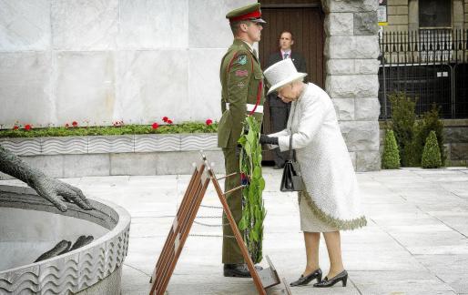 La monarca, en el acto más emotivo de la jornada, depositando una corona de flores en el Jardín del Recuerdo de Dublín.