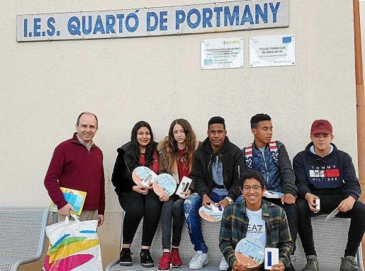 Imagen de los alumnos ganadores junto a su profesor, posando con los premios.