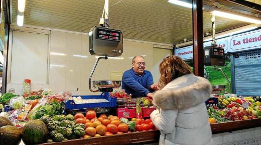 Juan Torres atiende en su puesto del Mercat Nou de Ibiza a una clienta «de toda la vida».