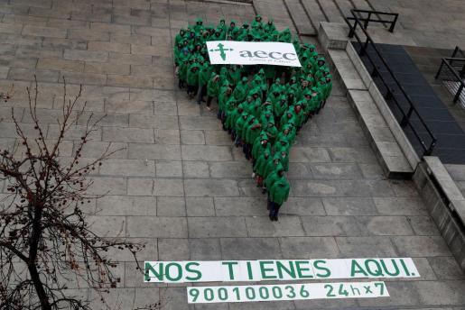 Varias personas vestidas de verde forman el símbolo de ubicación que representa la campaña de la AECC en la Plaza del Museo Reina Sofía de Madrid.