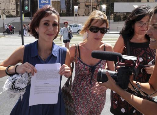 Juana Rivas (i), acompañada de su hermana Isabel (c), a la salida de los juzgados de La Caleta de Granada, enseña la orden de puesta en libertad provisional ordenada por un juzgado de guardia.