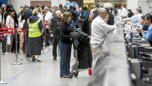 Varios pasajeros británicos hacen cola para confirmar la salida de sus vuelos en dirección a aeropuertos afectados por la nube volcánica.