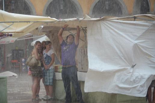 Un comerciante de la Plaza Mayor de Palma, en plena tormenta.