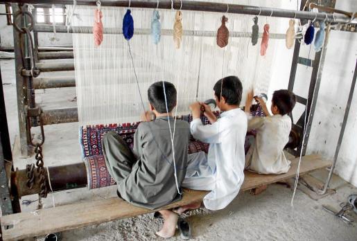 Un grupo de niños tejen una alfombra en una tienda en Chaman, en Pakistán.