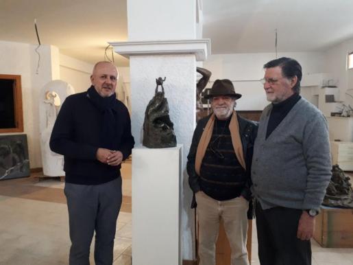 El presidente Ensenyat posa con la escultura en el taller del artista mallorquín.