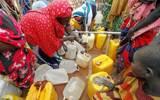 Imagen reciente de un grupo de mujeres somalís llenando depósitos de agua en un campo de refugiados de Kenia.