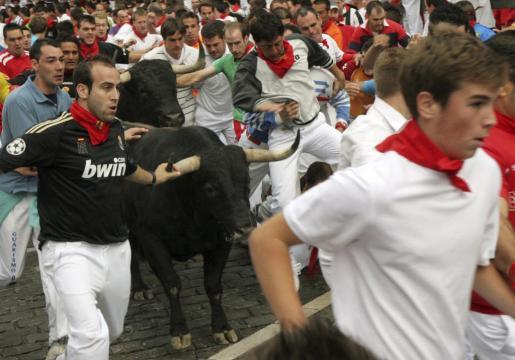 Un toro de la ganadería sevillana de Dolores Aguirre crea una situación de peligro a su paso por la curva de Telefónica durante el tercer encierro de los sanfermines 2011.