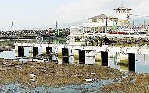 Los operarios han vaciado el agua del puerto y han construido un muro de contención para realizar los trabajos de limpieza. Foto: JAUME MOREY