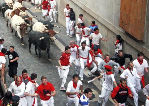 PAM09 PAMPLONA, 10/07/2011.- Mansos y morlacos entran agrupados en el tramo del Ayuntamiento produciendo bonitas carreras de los mozos, durante el cuarto encierro de los Sanfermines, con toros de la ganadería sevillana de Miura, que ha sido rápido y limpio, haciendo así gala de su fama de nobles, en un día que al ser festivo ha reunido a un multitudinario número de corredores. EFE/Josu Santesteban