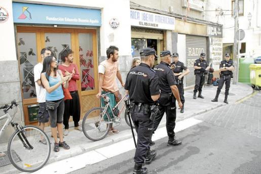 El grupo de indignados y la desahuciada, vestida de azul, frente a la Policía.