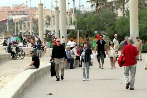 Algunos turistas pasean por la Playa de Palma.