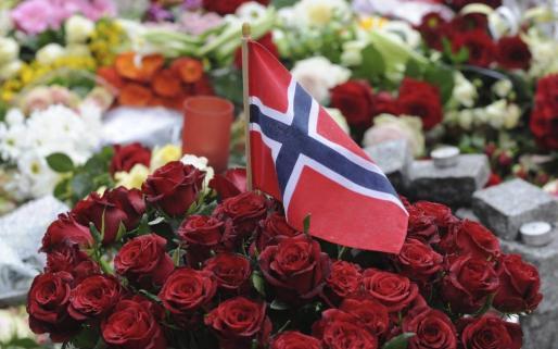 Detalle de la bandera noruega entre unas flores depositadas en el exterior de la catedral de Oslo, Noruega, para mostrar respeto a las víctimas de los dos ataques sufridos en el país.