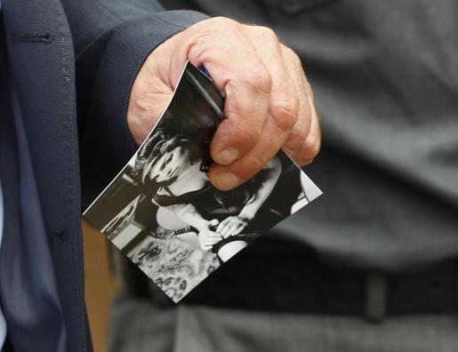 Un asistente al funeral con una foto de la cantante.