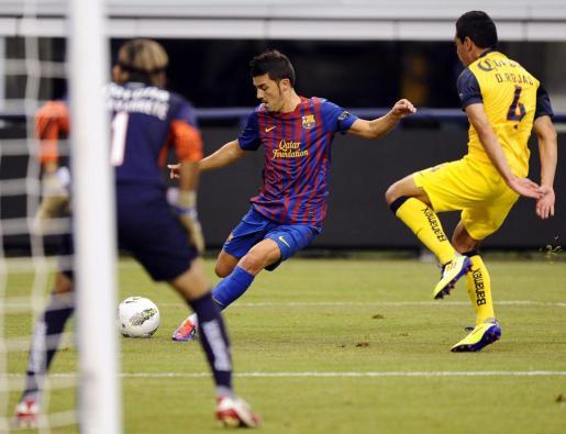 El jugador del FC Barcelona David Villa (C) dispara el balón para anotar un gol ante el Óscar Rojas (d) del América.
