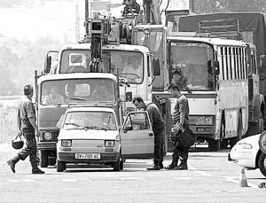 La policía macedonia, efectuando, ayer, un control en los alrededores de Skopje.