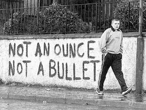 Un niño pasa por delante de una pintada en contra del desarme del IRA.