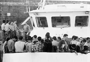 Un grupo de inmigrantes espera ser trasladado a los módulos de acogida en Tarifa.