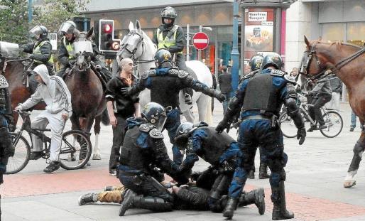 Dos agentes esposan a un hombre en Manchester en medio de un gran despliegue policial.