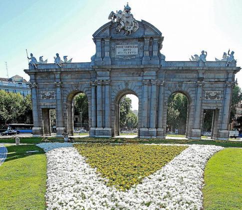 Flores blancas y amarillas, los colores vaticanos, en la Puerta de Alcalá para recibir al Papa.