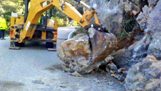 Una máquina retirando las rocas de la calzada.