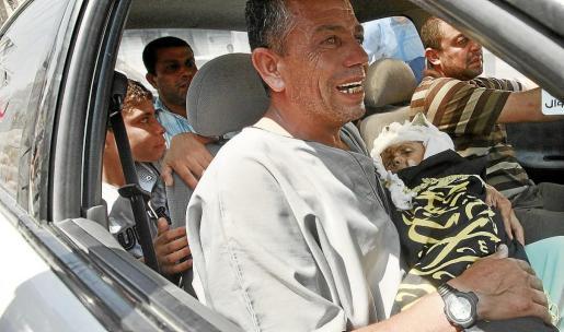Un hombre lleva en brazos a su hijo de dos años muerto por los bombardeos en Gaza.