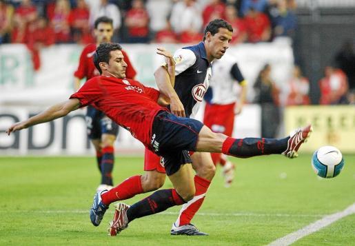 José Izquierdo pugna por el balón con Maxi Rodríguez durante un encuentro entre Osasuna y Atlético de Madrid.