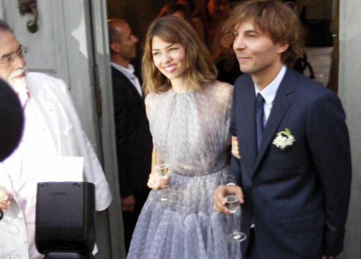 """La directora de cine estadounidense Sofía Coppola (c) y el líder de la banda de rock francesa """"Phoenix"""", Thomas Mars (d), posan para los fotógrafos después de su boda en Bernalda, Italia."""