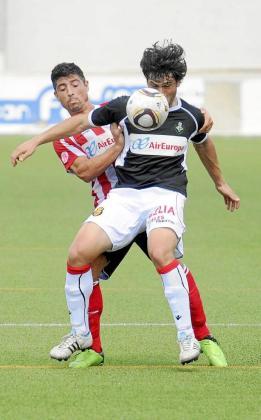 El mallorquinista Flores, que debutó ayer en Manacor, defiende el balón ante la presión de Julio Huertas.