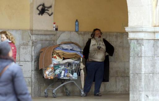 El indigente, días atrás, bajo los arcos del Mercat de l'Olivar, donde estaba siempre.