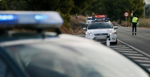 Un agente de la Guardia Civil da el alto a un vehículo en un control de tráfico.