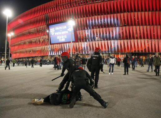 Agentes de la brigada móvil de la Ertzaintza, detienen a un aficionado tras varias cargas momentos antes de comenzar el partido entre el Athletic Bilbao- Spartak de Moscú.