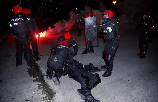 Agentes de la brigada móvil de la Ertzaintza atienden a un compañero herido tras varias cargas con aficionados momentos antes de comenzar el partido entre el Athletic Bilbao- Spartak de Moscú.