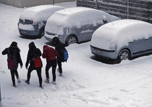 Un grupo de estudiantes caminan entre la nieve que se ha acumulado durante la madrugada en Pamplona.