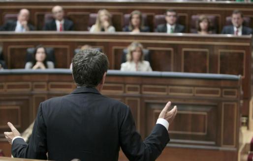 El presidente del Gobierno, José Luis Rodríguez Zapatero (de espaldas), responde a la pregunta del líder del PP, Mariano Rajoy.