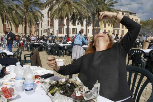 Una mujer, comiendo uno de los calçots.