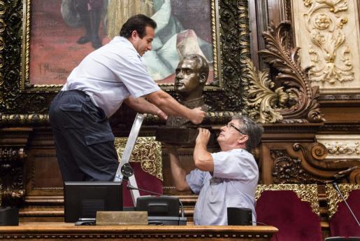 Imagen de archivo de dos operarios municipales retirando el busto del Rey Juan Carlos del Ayuntamiento de Barcelona.