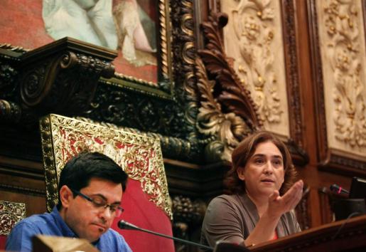 La alcaldesa de Barcelona, Ada Colau, y el primer teniente alcalde, Gerardo Pisarello, durante el pleno del consistorio barcelonés, delante del cuadro de la reina regenta María Cristina y la repisa en la que se encontraba el busto del rey Juan Carlos I que fue retirado por orden del gobierno municipal.
