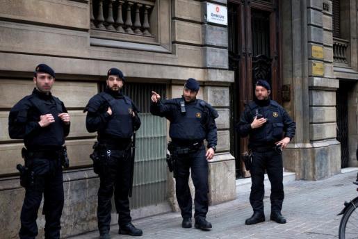 Los Mossos d'Esquadra custodian la sede de Òmnium Cultural en Barcelona, donde la Guardia Civil ha efectuado un registro por orden judicial.