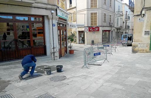 Un operario sustituye una losa deteriorada en una calle del centro de Muro, esta semana.