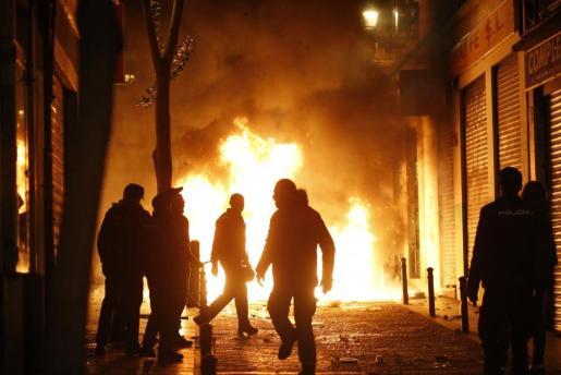 Contenedores incendiados en el barrio de Lavapiés de Madrid, tras la muerte de un mantero de un paro cardíaco durante un control policial contra el top manta.