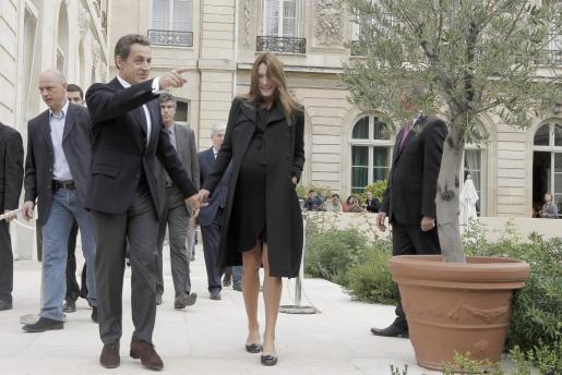 La primera dama Carla Bruni (dcha) pasea junto a su marido el presidente francés Nicolas Sarkozy (izda) por los jardines del Palacio del Elíseo en París.