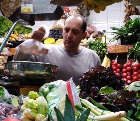 Juanjo rodeado literalmente de frutas y verduras, frescas, locales y tratadas con mucho cariño.