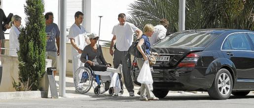 Un celador lleva a la actriz norteamericana Halle Berry en silla de ruedas hasta el coche que la esperaba junto a una de las puertas traseras de la Policlínica Miramar.