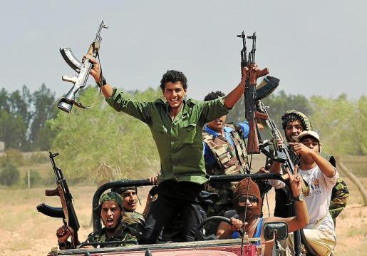 Soldados rebeldes exhiben victoriosos sus armas muy cerca de Sirte.