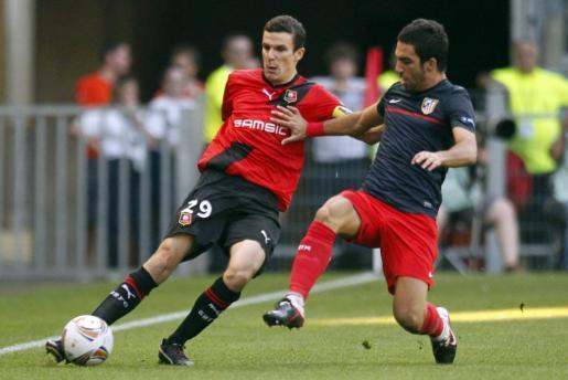 Romain Danze (izq.), del Rennes, lucha por un balón con Diego, del Atlético de Madrid durante el partido disputado hoy.