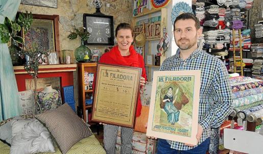 La propietaria, Vicky Sánchez, y Pere Soler muestran dos antiguos cuadros publicitando el comercio de La Filadora.
