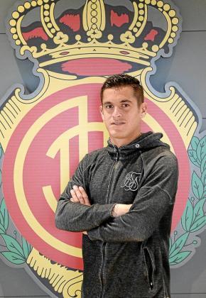 Marc Pedraza posa frente a un escudo del Mallorca.