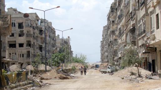 Dos personas caminan entre las ruinas de la ciudad de Zamalka en Guta Oriental, cerca de Damasco (Siria).