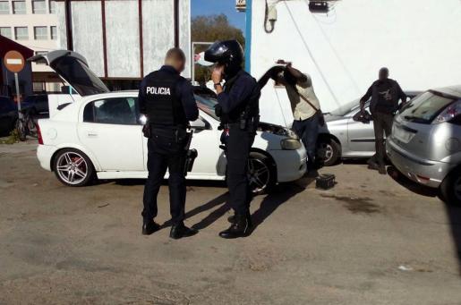 Una decena de agentes de la Policía Local de Palma inspeccionando los vehículos utilizados como talleres y almacenes móviles.