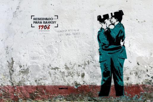 La imagen de dos guardias civiles besándose replica casi exactamente a la de dos policías británicos besándose que Banksy realizó cerca del centro de Brighton.
